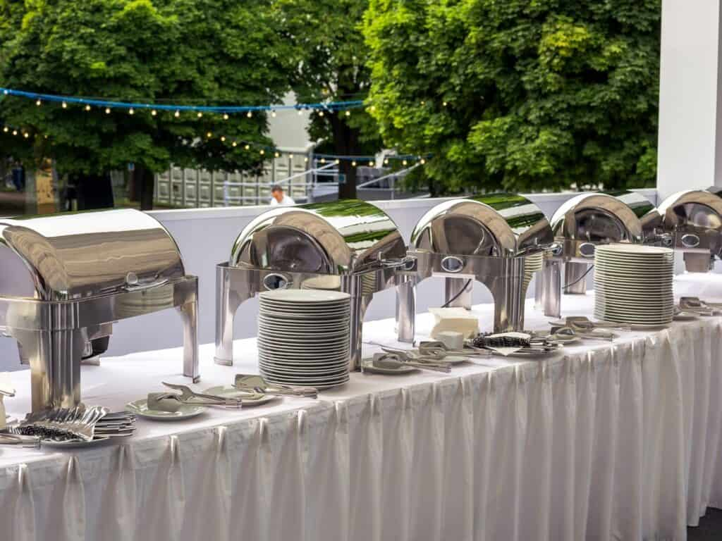 chafing dishes on a long buffet table with plates