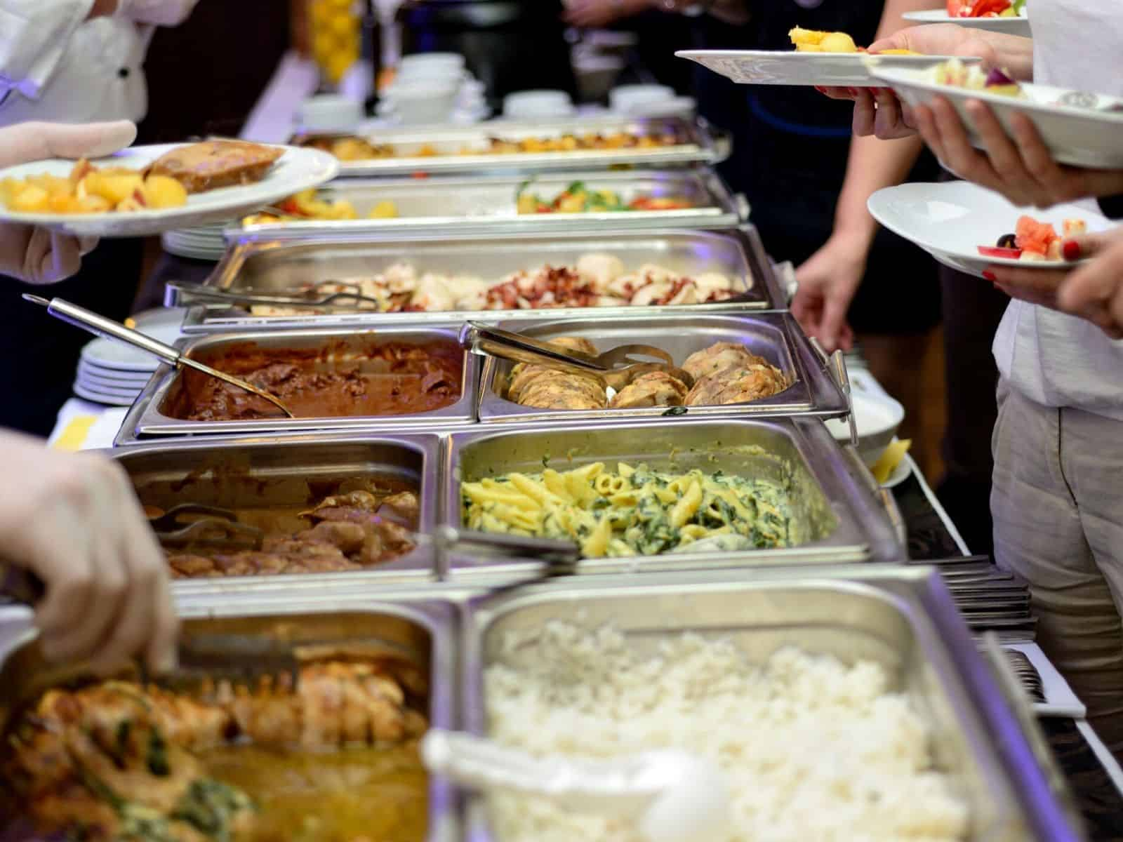 chafing dishes set up on a buffet table with warm food and people serving themselves