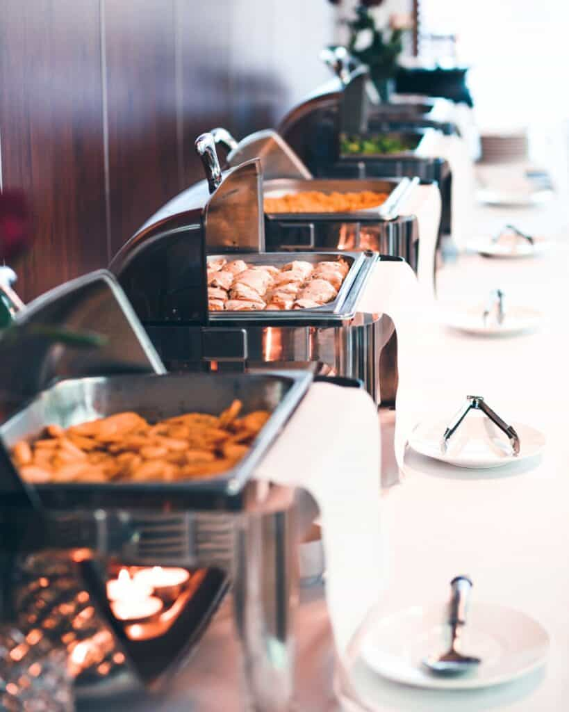 chafing dishes on buffet table with food inside