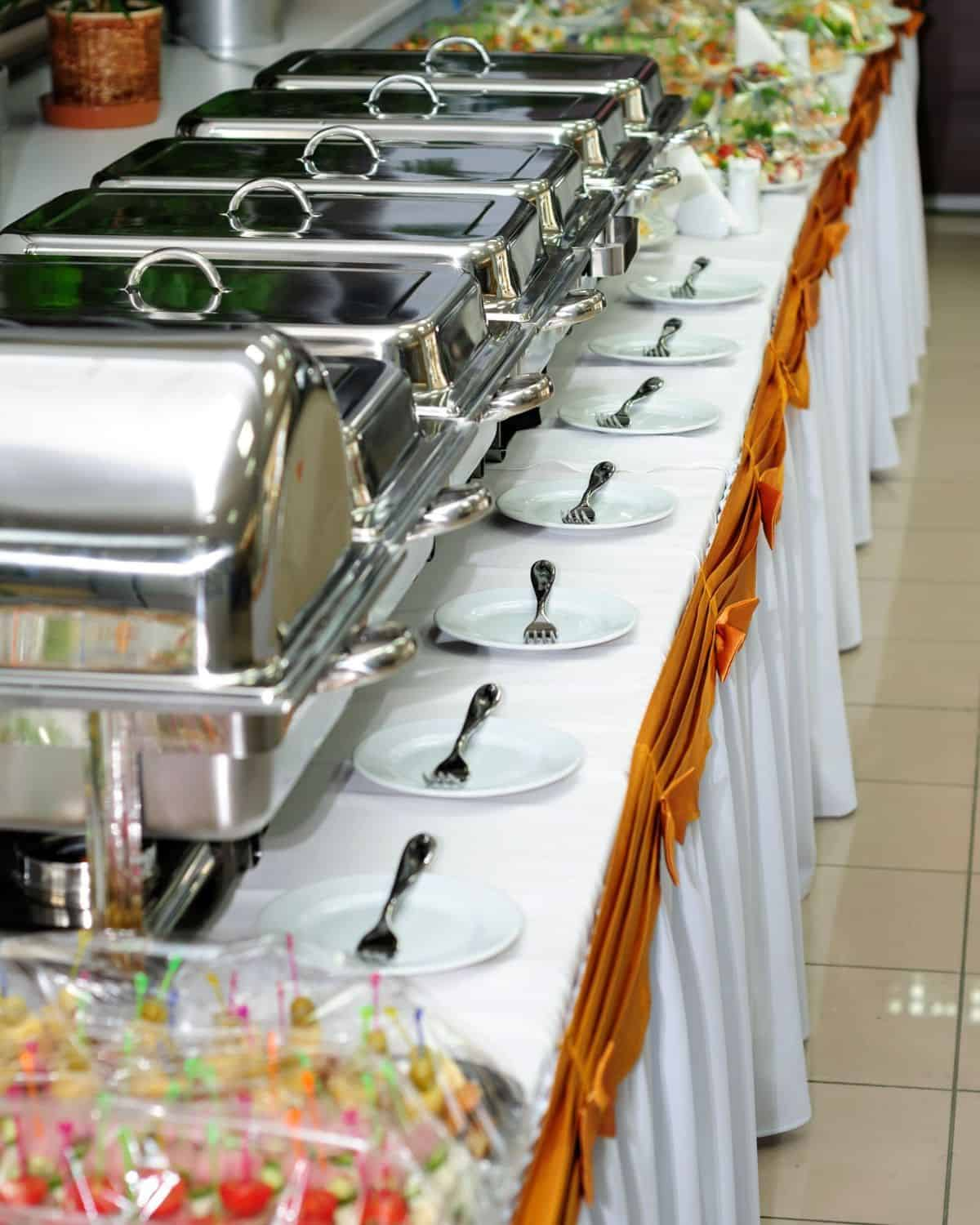 a buffet station set up with chafing dishes on a long table.