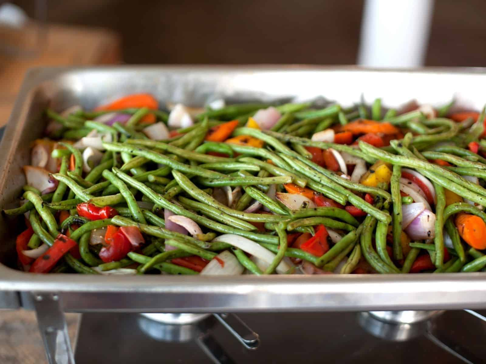 chafing dish with green beans and veggies.