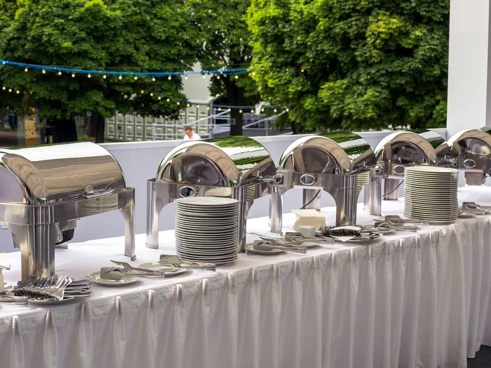 chafing dishes on a long buffet table with plates.