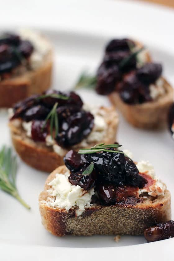 grape and goat cheese crostini on a plate.