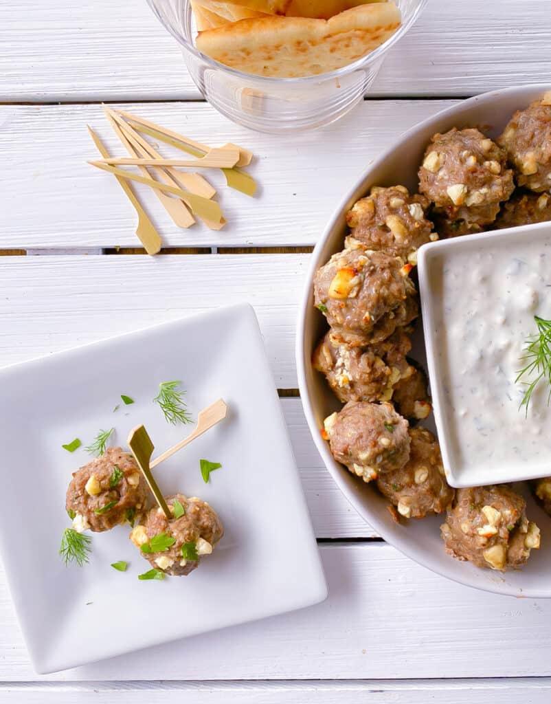 lamb feta stuffed meatballs overhead shot of plate and bowl of tzatziki sauce