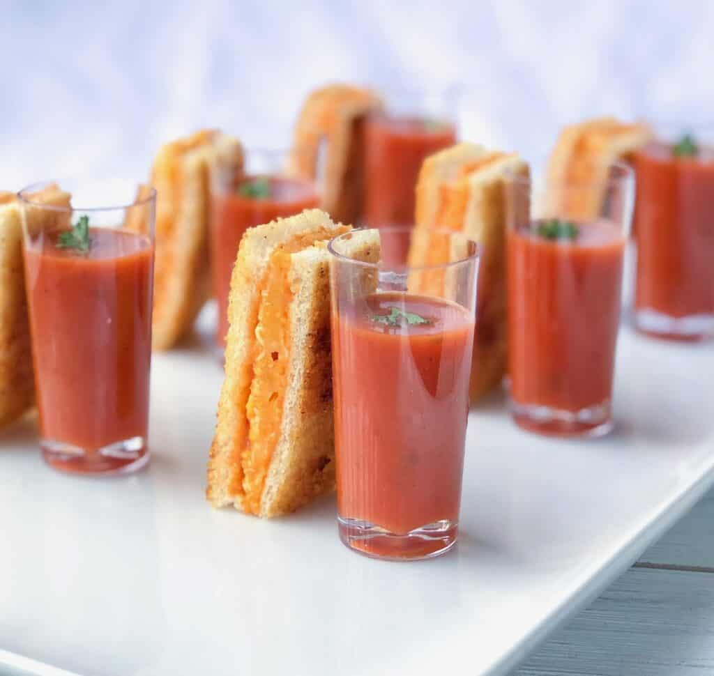 grilled cheese sticks with tomato soup hors d'oeuvre shooters on a white plate.