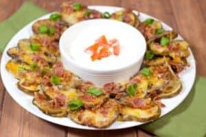irish potato nachos on a white plate with sour cream.