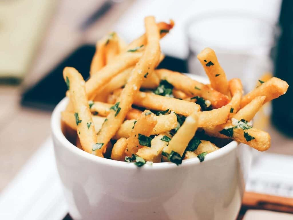 french fries in a bowl with herbs on top