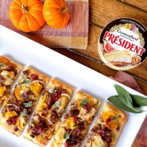 sausage and pumpkin flatbread appetizer on plate with sage
