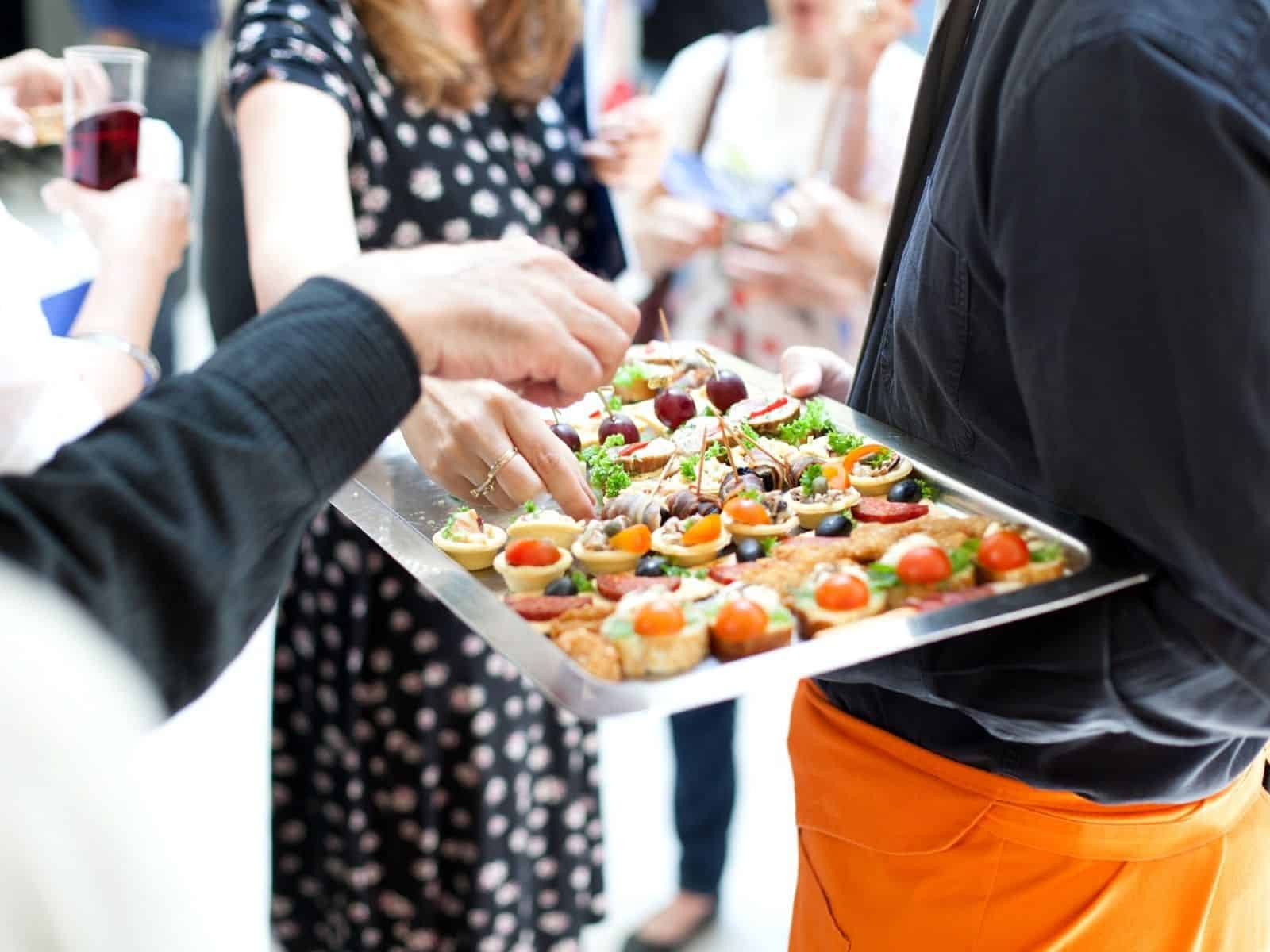 a caterer serving hors d'oeuvres at an event.