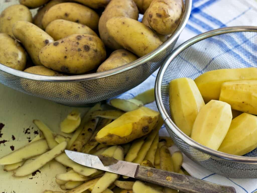 yellow potatoes cut and peeled in strainers