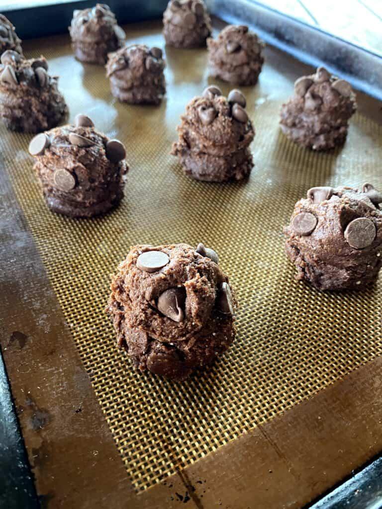 raw chocolate cake mix cookie balls on baking sheet