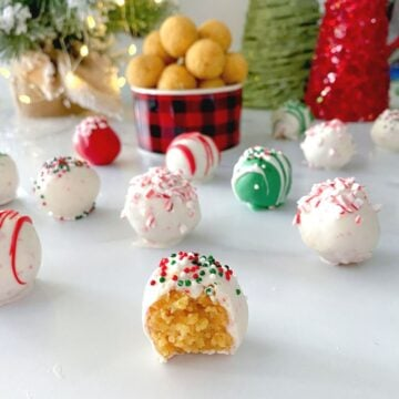 yellow cake balls coated in candy melts chocolate on a table.