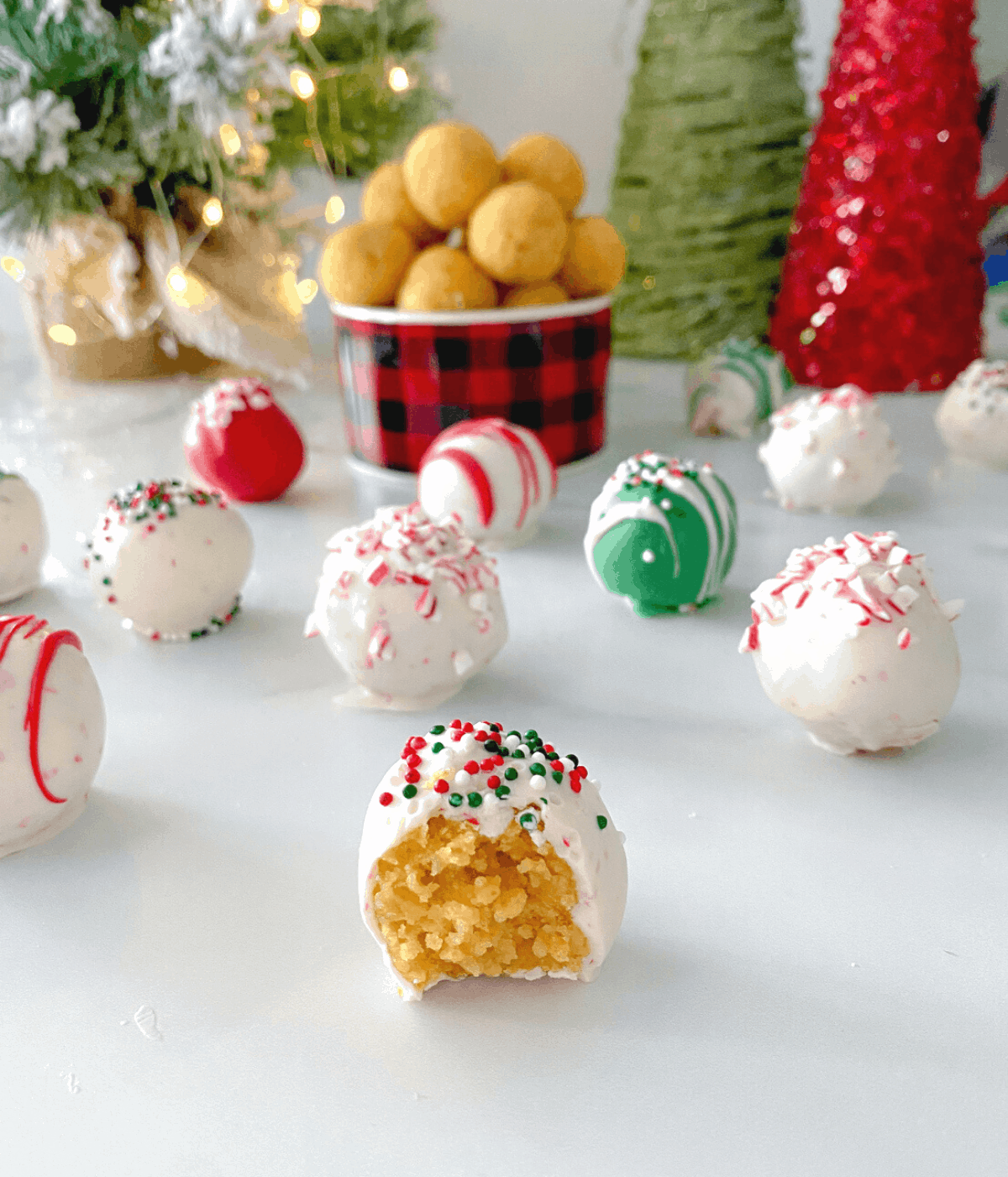 Christmas cake balls on a table coated in white chocolate candy melts with decorations in the background.