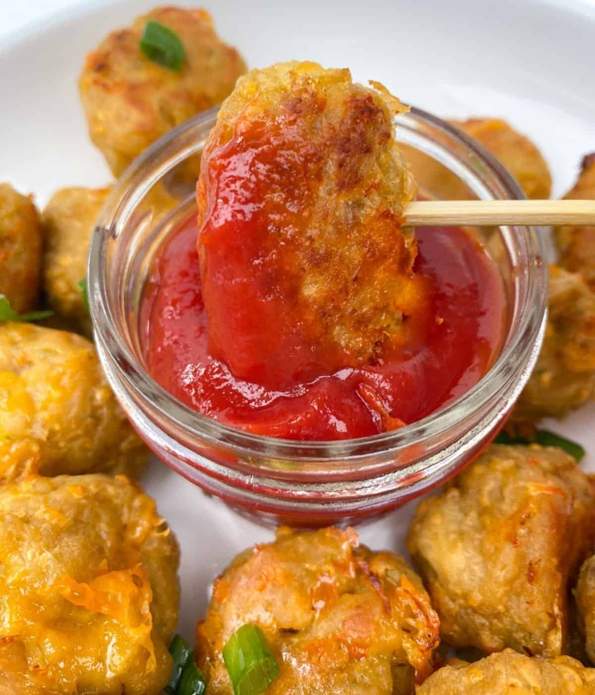 Sausage ball with ketchup on skewer.