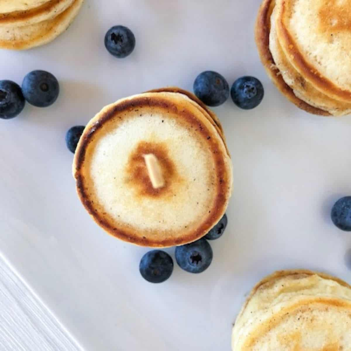 overhead shot of mini silver dollar pancakes with blueberries around them.