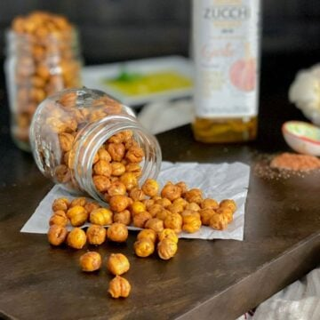 roasted garlic chickpeas spilling onto a cutting board