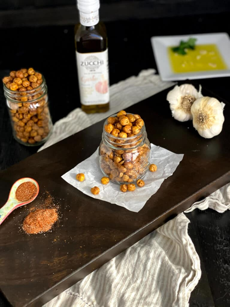 roasted chickpeas in a mason jar with spices and garlic around