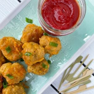 sausage balls without pancake mix on a plate with ketchup and skewers.