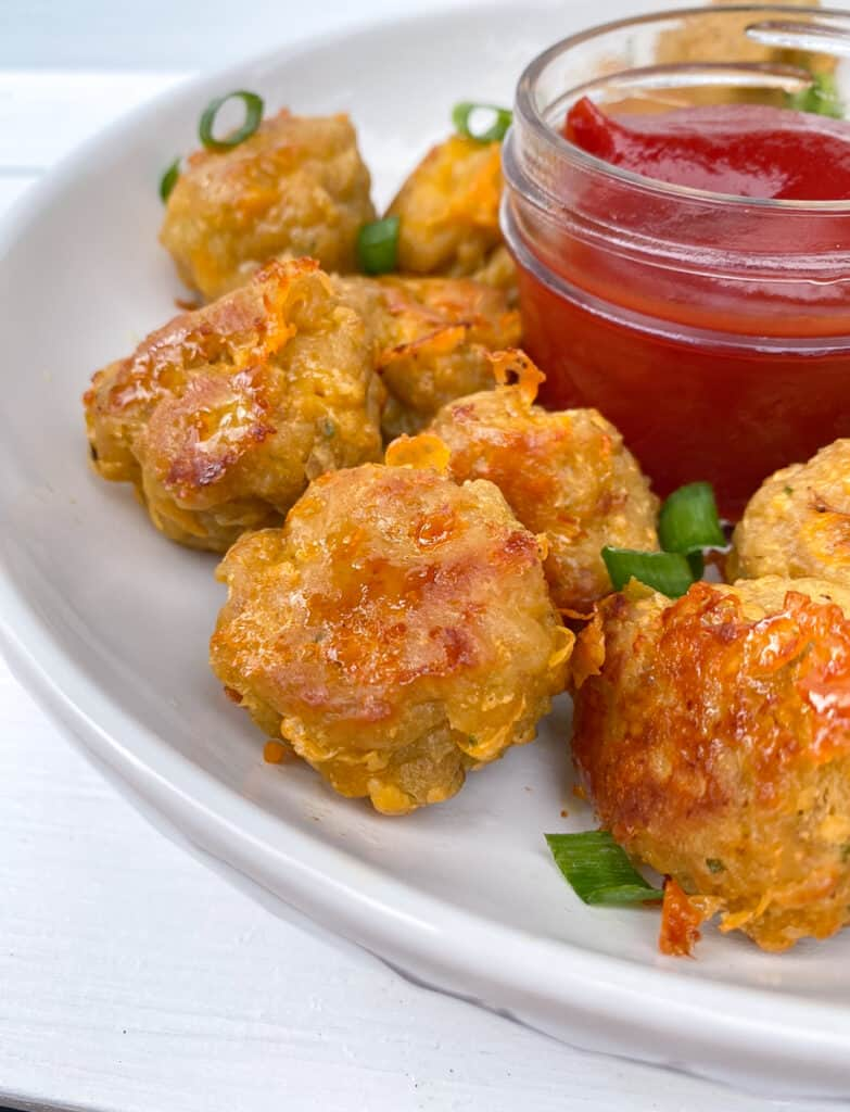 Sausage balls on a plate around ketchup for dipping.