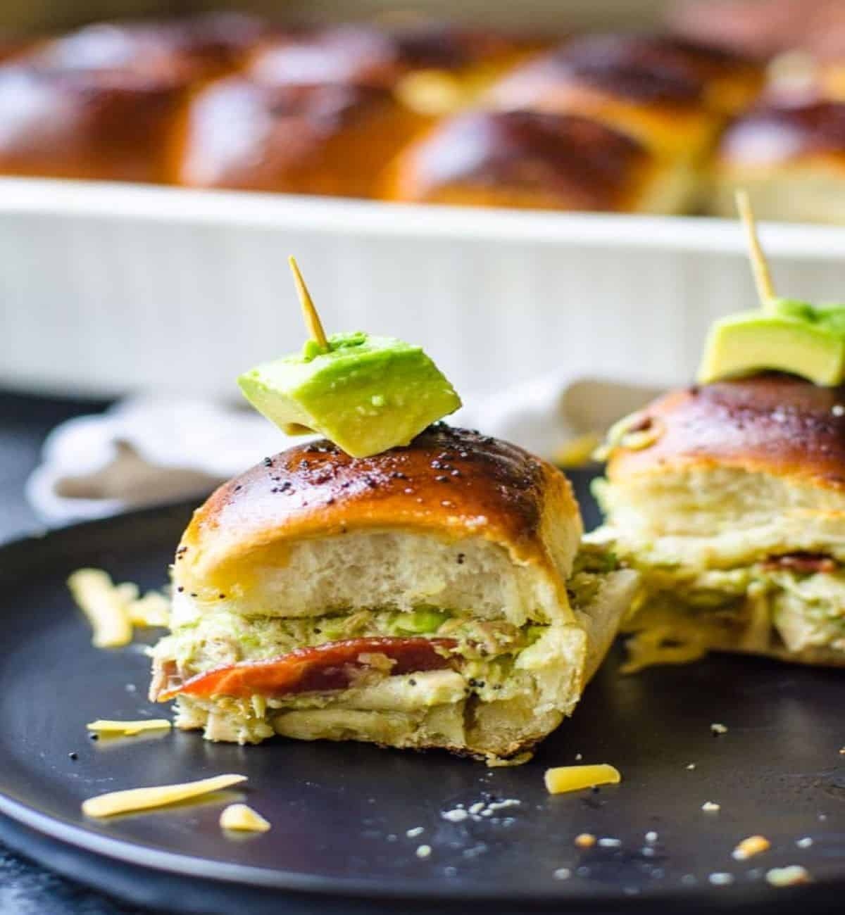 hawaiian turkey sandwich slider on a slate with toothpicks.