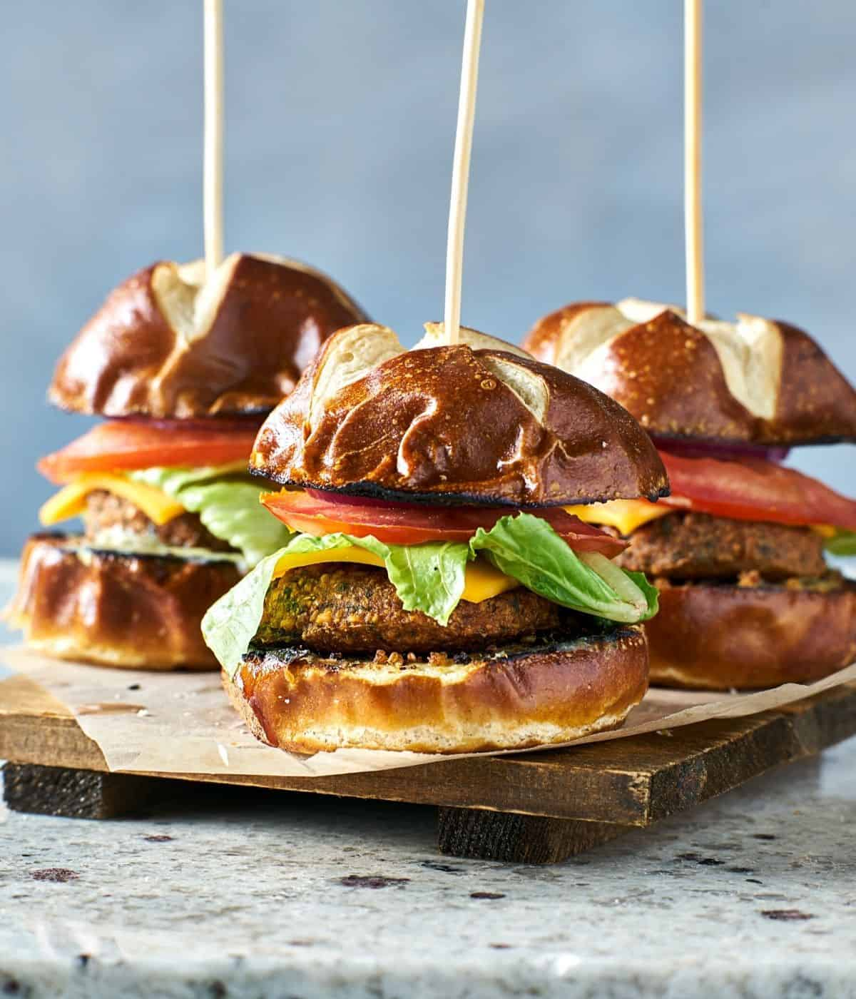 Mini party sandwich sliders on a wood plank with skewers.