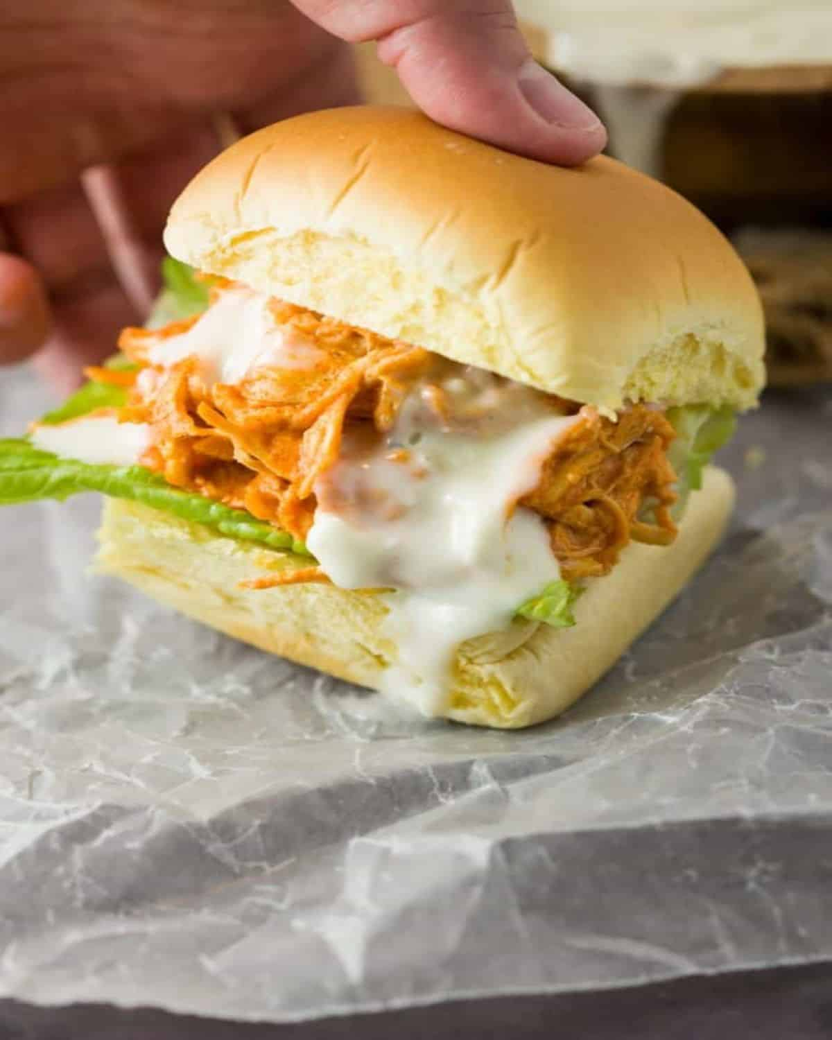 chicken honey mini party slider on wax paper with melted cheese.