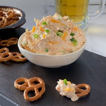 beer cheddar cheese dip with pretzels on a cutting board.