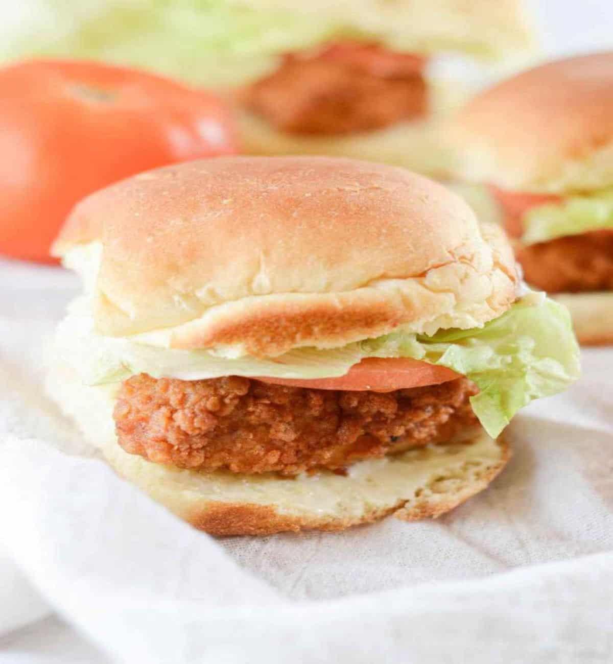 mini crispy chicken slider with lettuce and tomato on a bun.