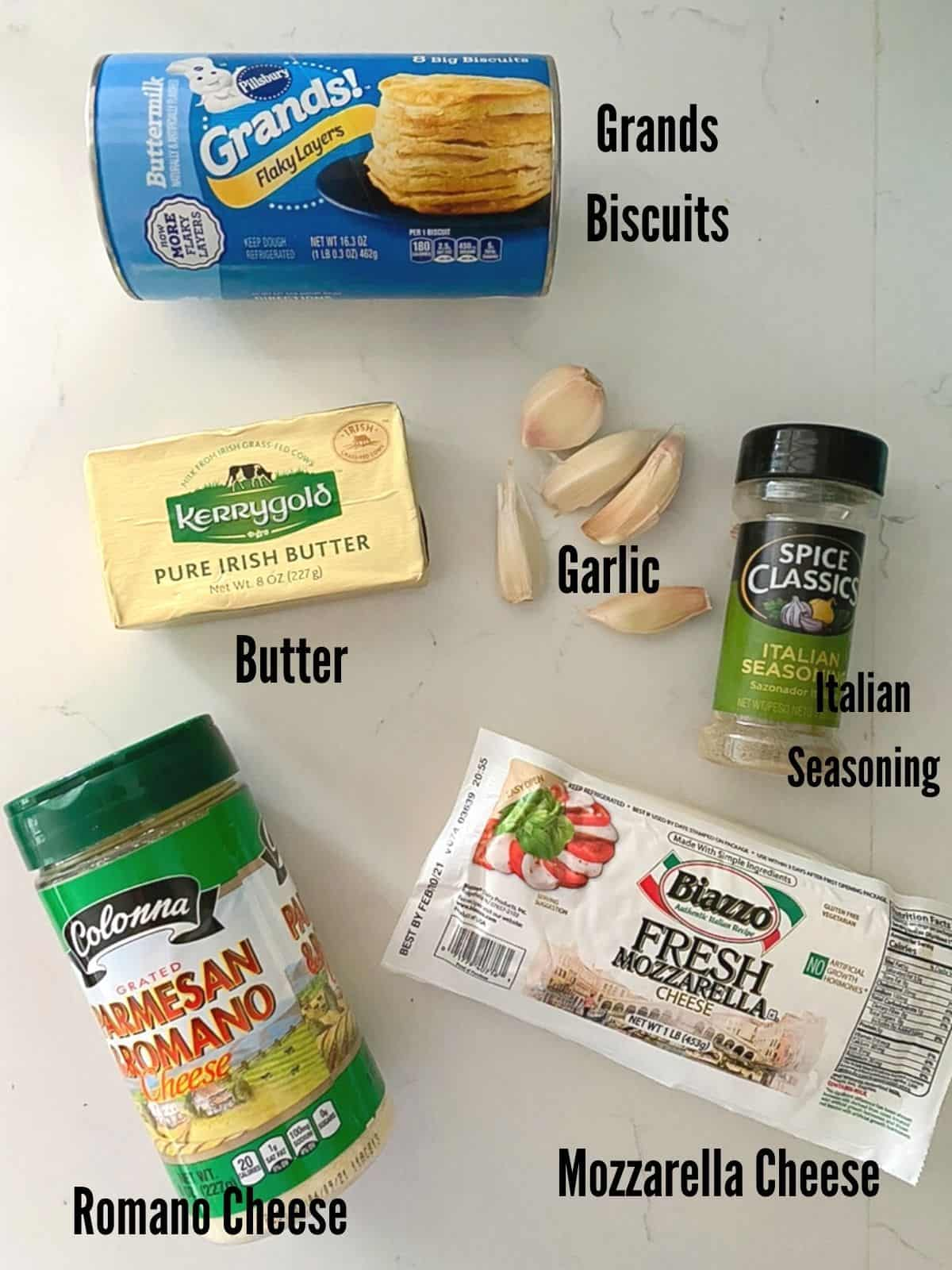 Ingredients to make cheesy stuffed garlic biscuit bombs laid out on table.