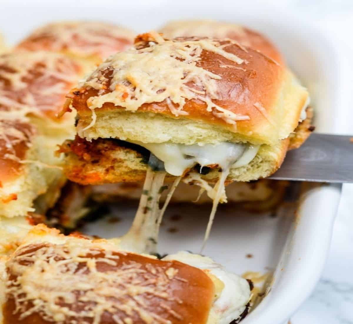 mini chicken parm pesto slider being pulled out of casserole dish.