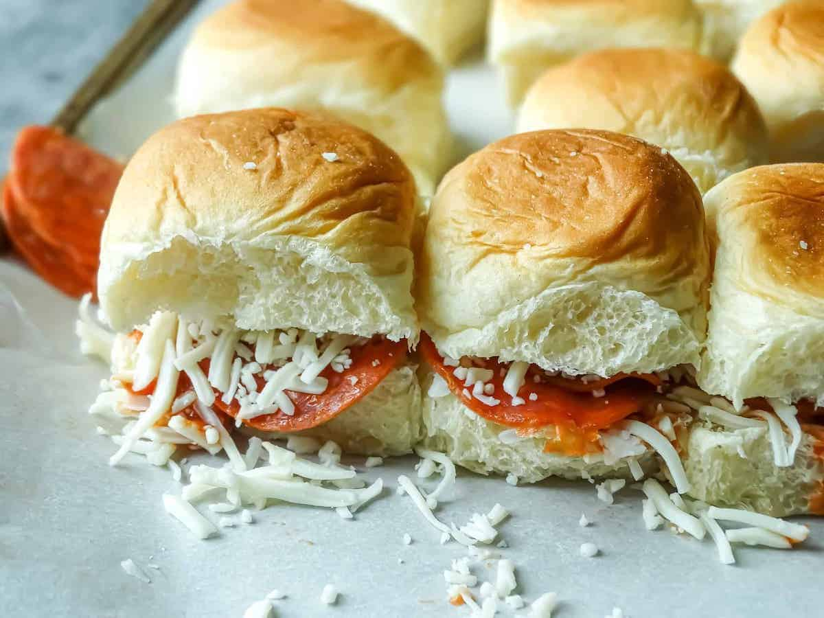 mini pepperoni slider sandwiches with shredded mozzarella cheese on baking sheet.