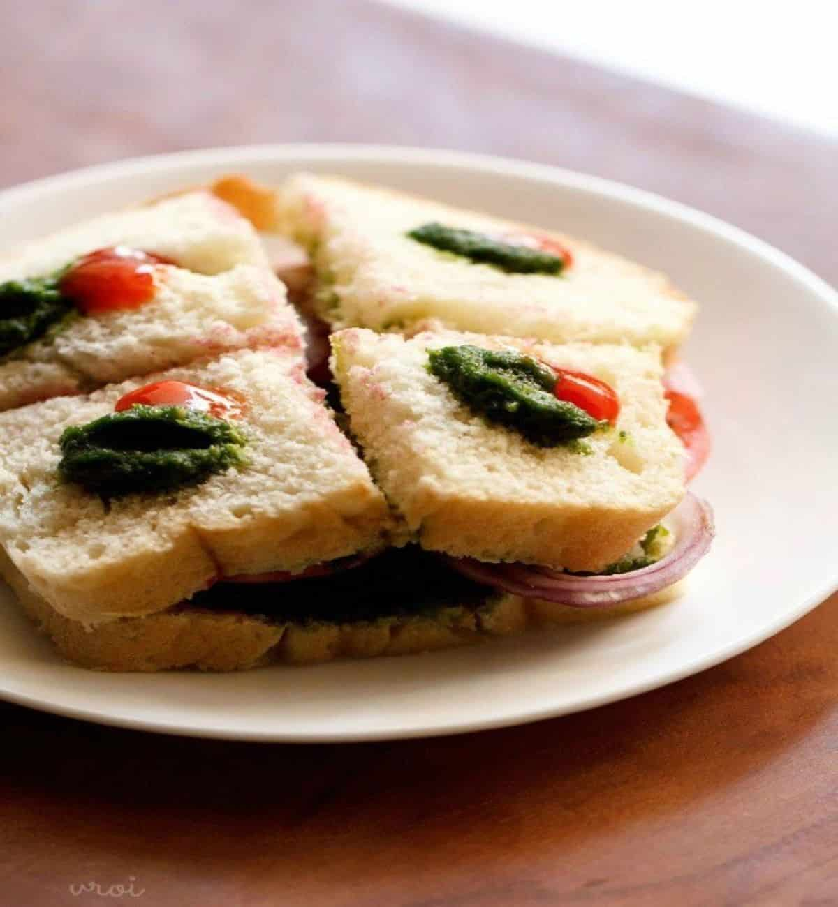 one bite mini bombay sandwiches on plate topped with pesto.