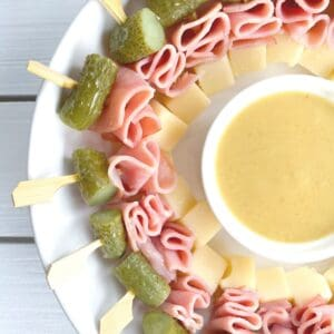 skewered ham cheese and pickle appetizer on a plate with dipping sauce in center.