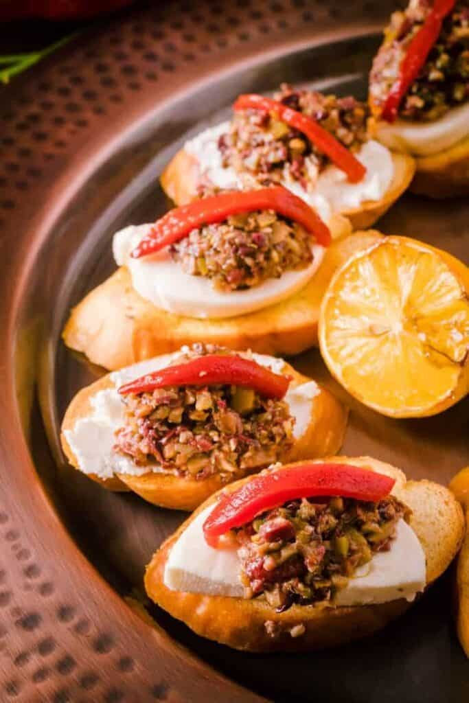 olive tapenade crostini with lemon on the side.