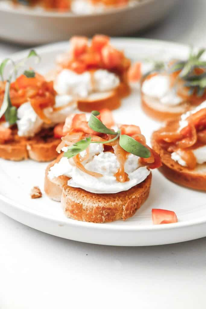 crostini with burrata and tomatoes on plate.