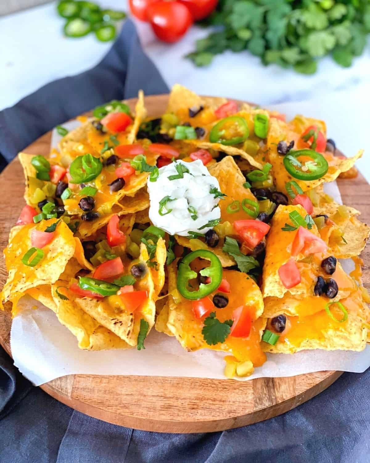 nachos air fried with cheese, tomatoes, jalapenos, beans and sour cream on a cutting board.