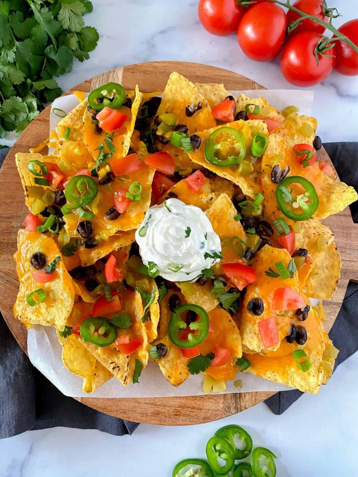 cheesy loaded air fryer nachos on a round cutting board with cheese, tomatoes, black beans, jalapenos and sour cream.