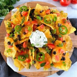 air fryer nachos with cheddar cheese, beans, tomatoes and sour cream on plate.