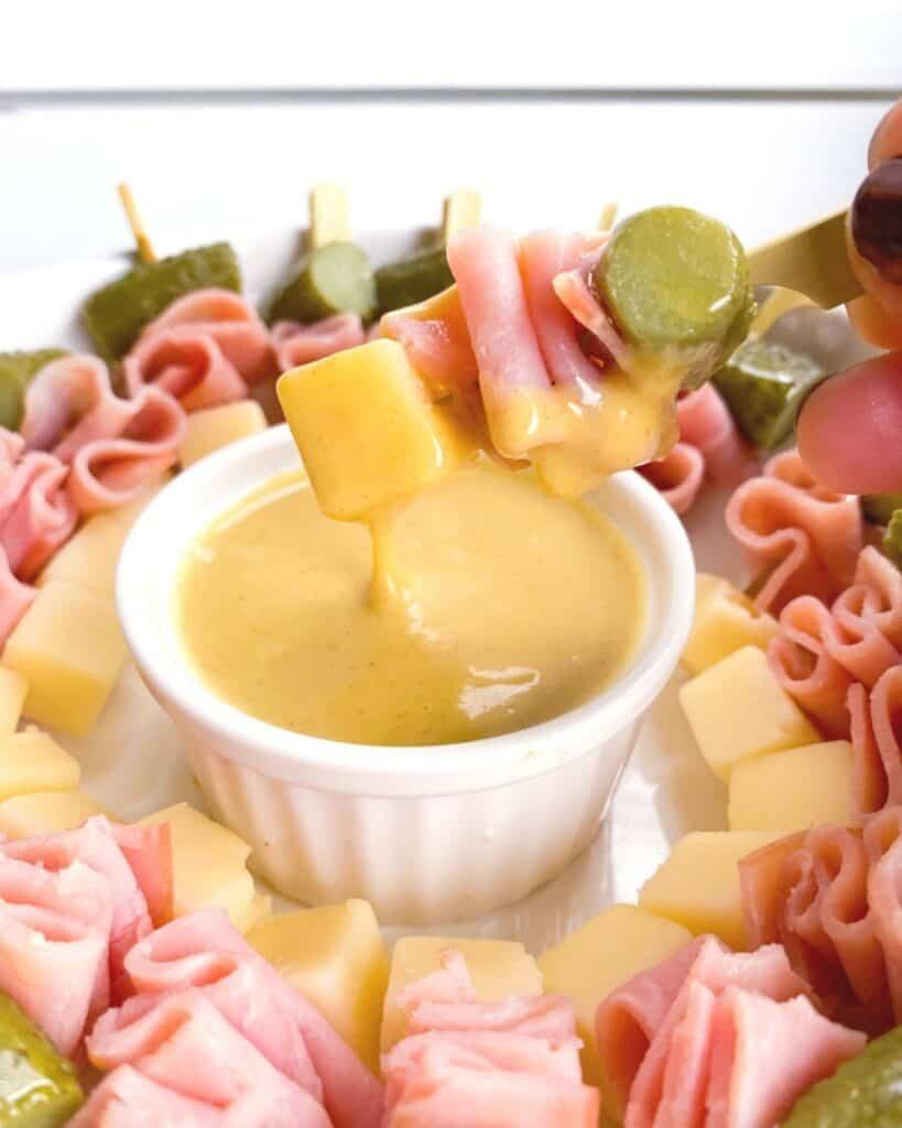 mini cubano skewers dipped in sauce.