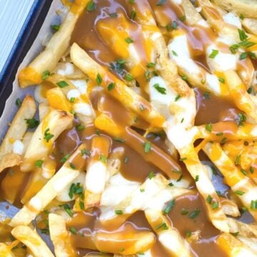 disco fries on a baking sheet with gravy.