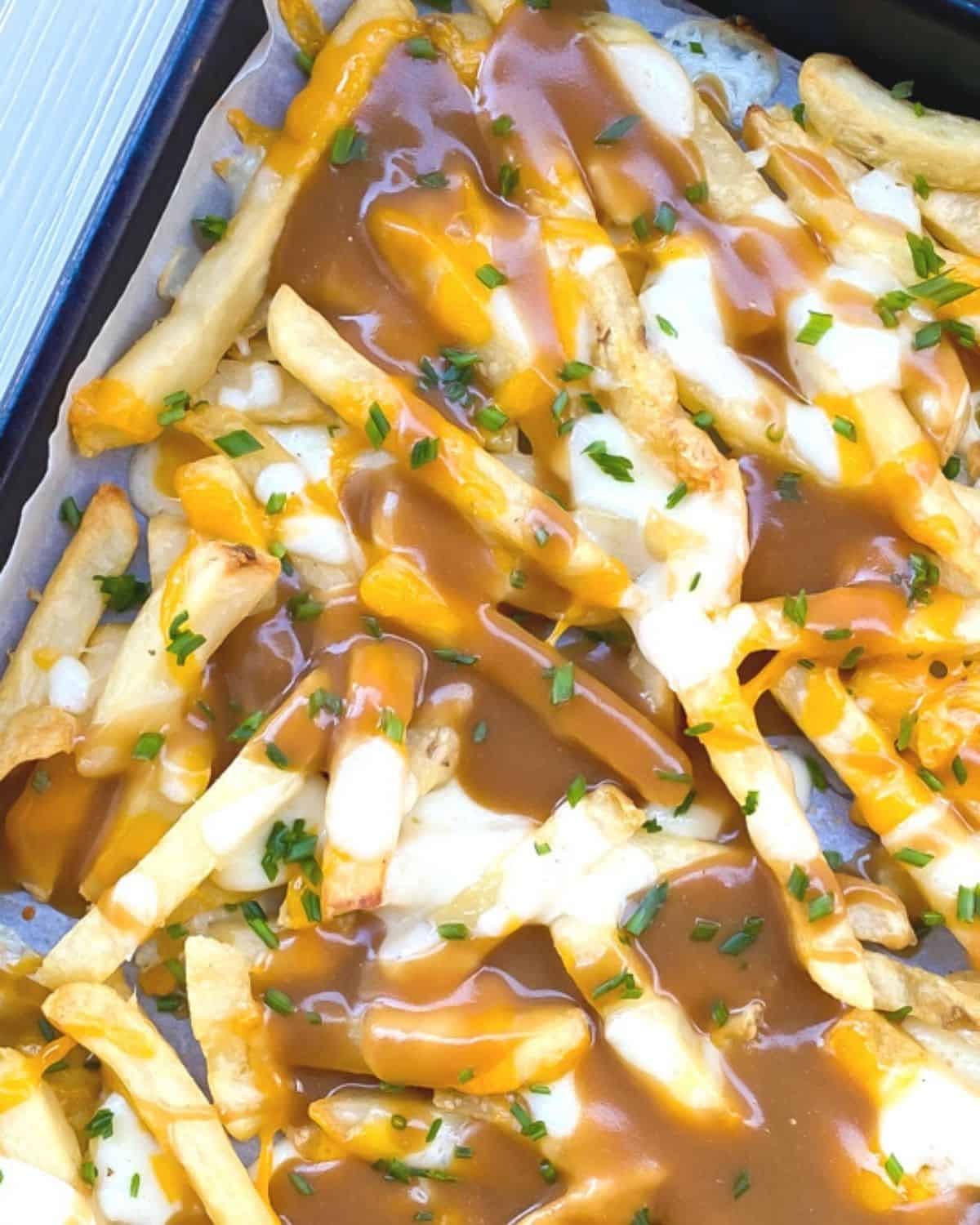 disco fries on a baking sheet smothered with gravy and mozzarella cheese.