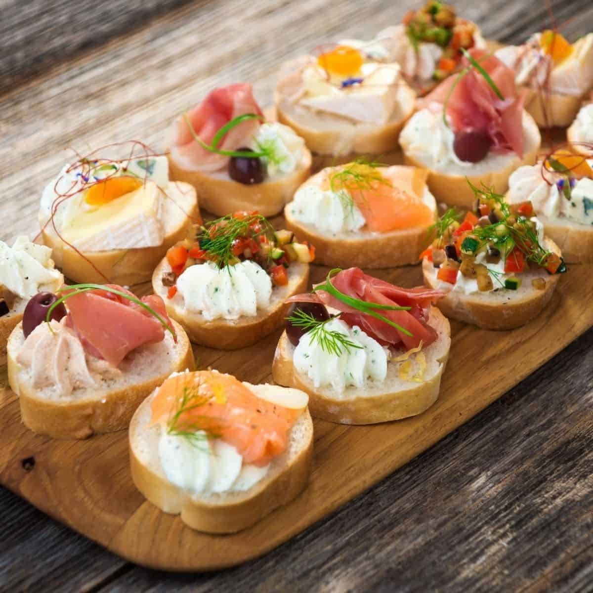 a selection of party finger food appetizers on a wooden board.