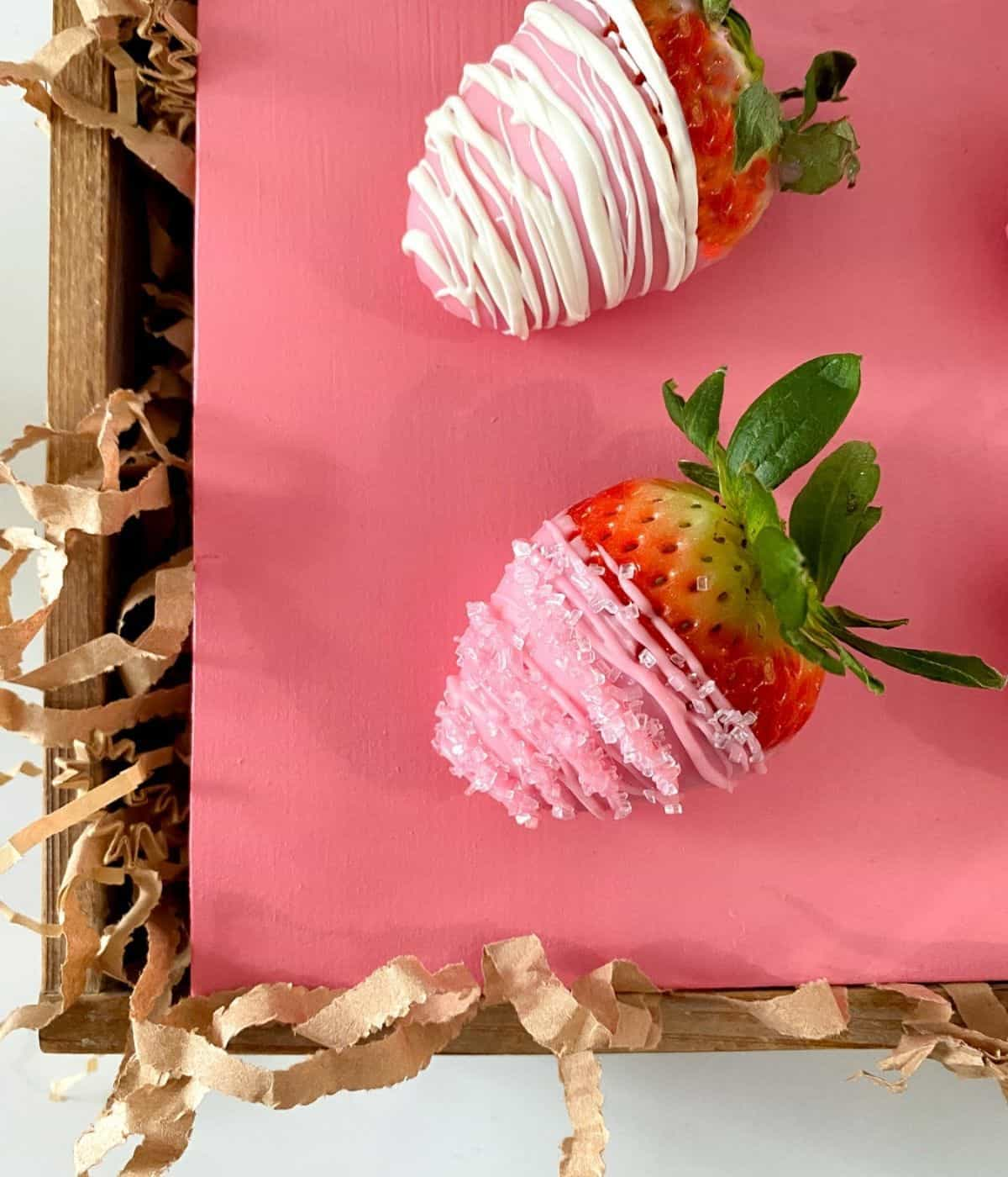 pink chocolate covered strawberries in a box with crinkle paper.