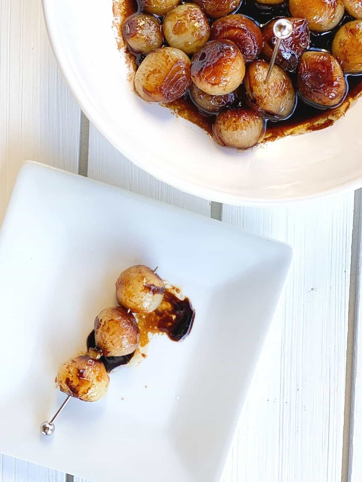 caramelized pearl onions on a plate with balsamic vinegar.