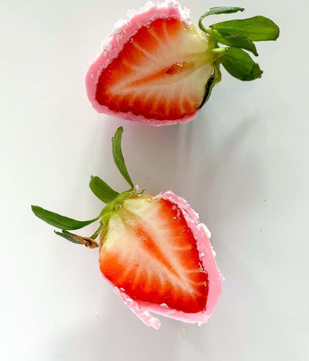pink chocolate covered strawberry sliced in half.