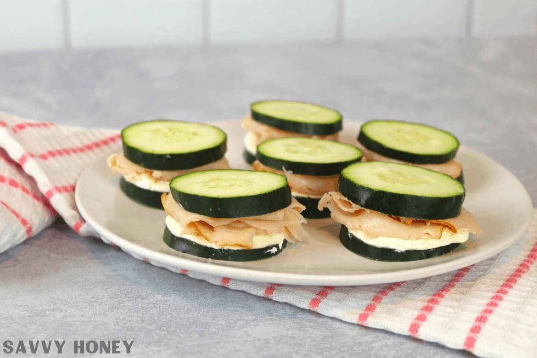 mini keto cucumber sandwiches on a plate.