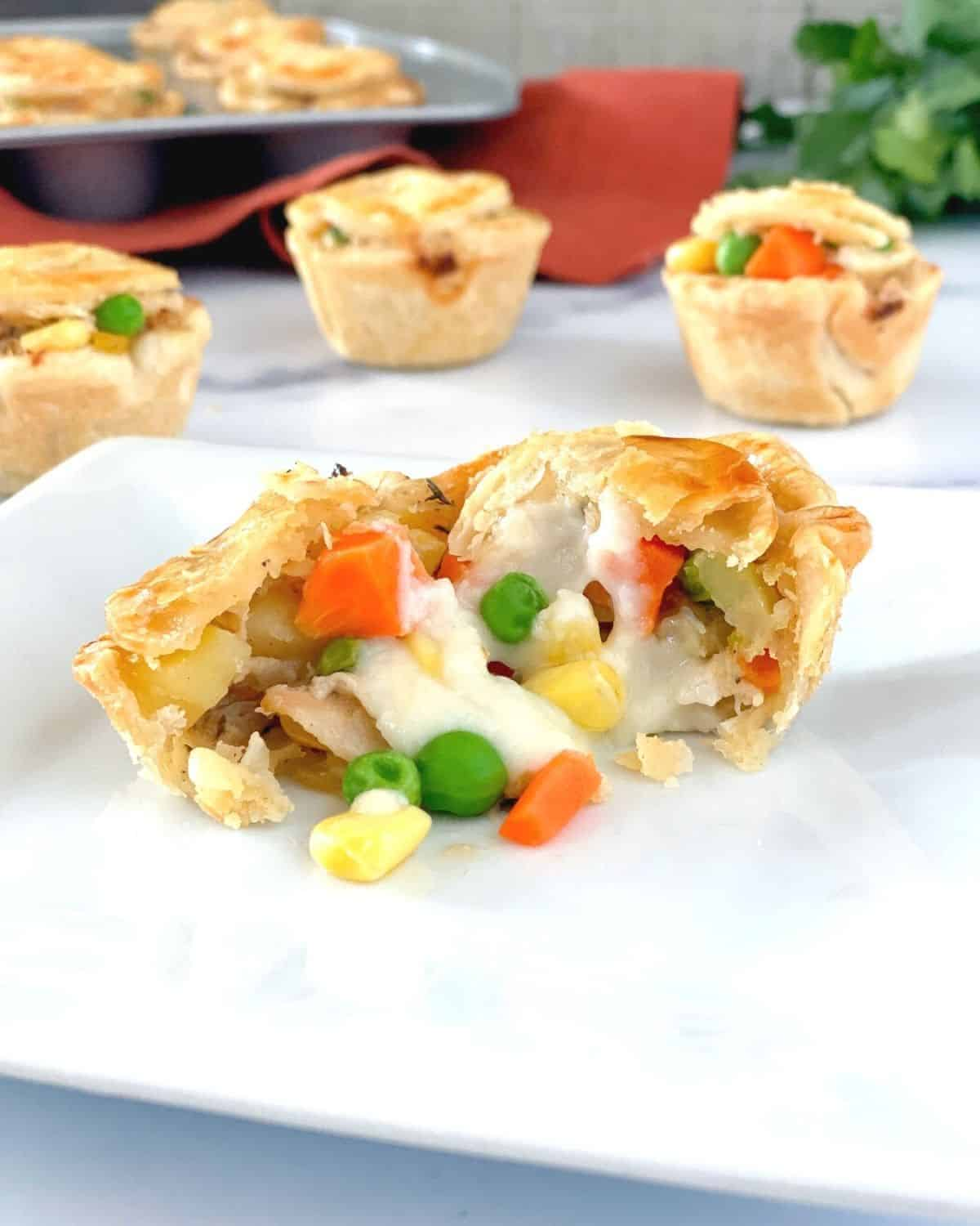 The inside of a mini chicken pot pie on a plate with veggies spilling out.