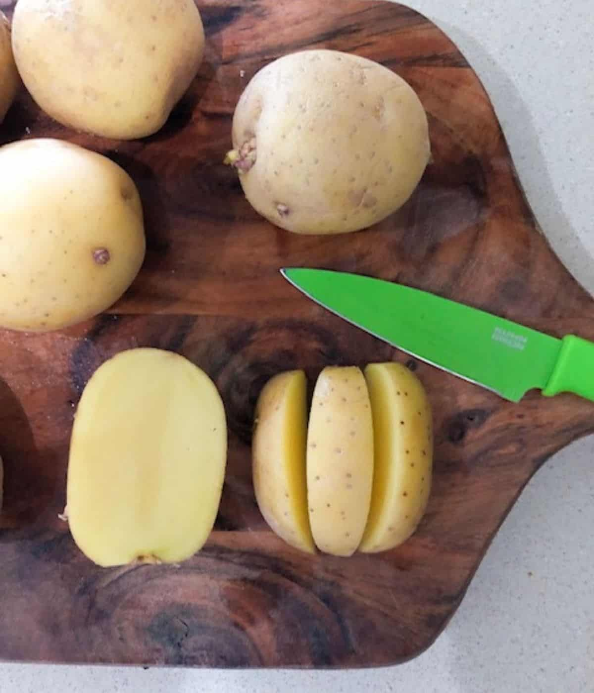 Showing how to cut potato wedges on a cutting board.