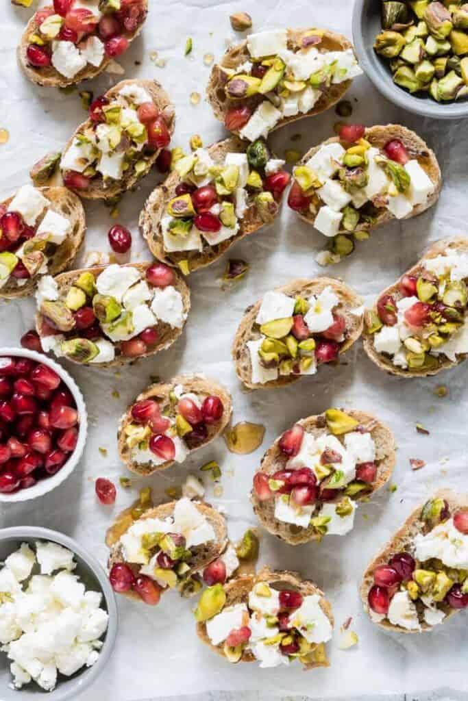 pistachio and feta crostini on a plate with pomegranates.