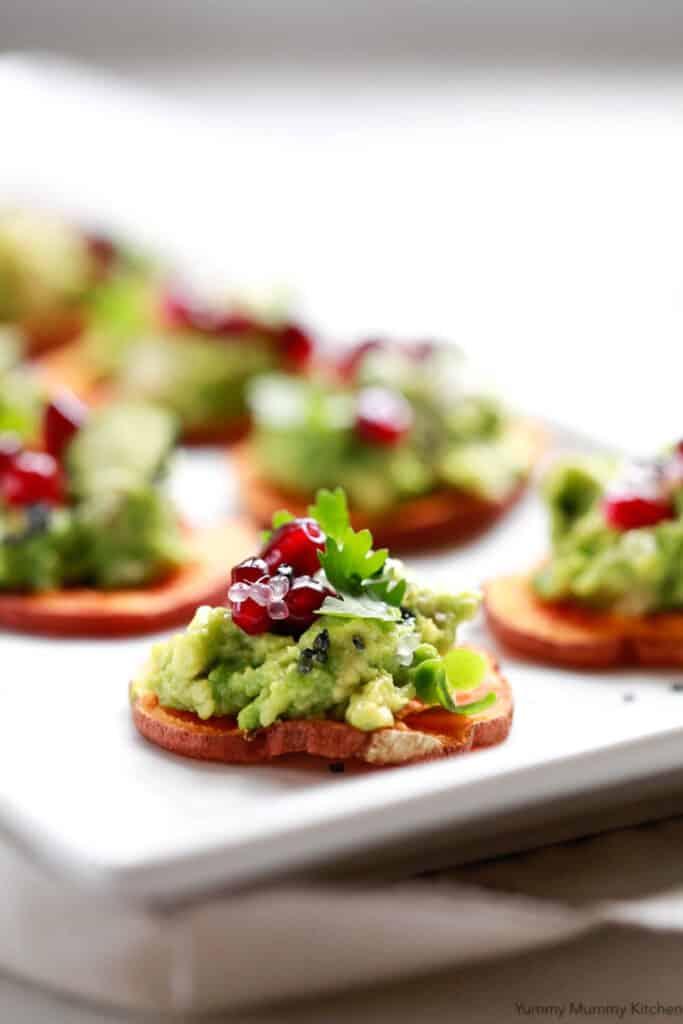 Mini sweet potato crostini with avocado on plate.